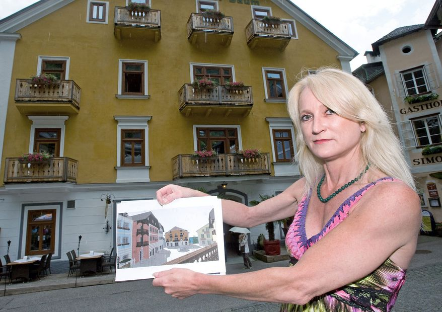 Monika Wenger, the owner of the Gruener Baum (Green Tree) hotel, shows a drawing by Chinese architects of her hotel in Hallstatt, Austria. After taking photos and collecting other data on the village while mingling with tourists, Chinese architects plan to rebuild Hallstatt in Guandong province.