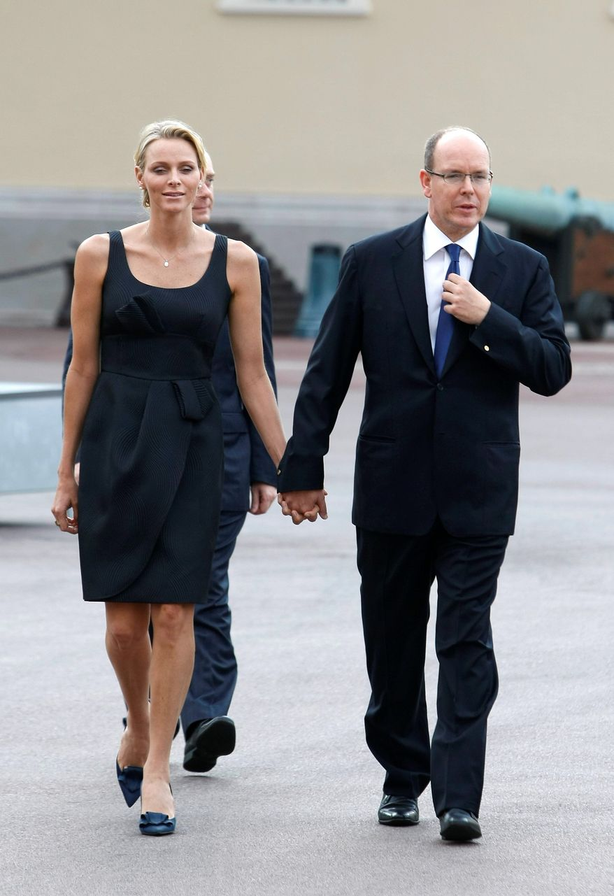 Prince Albert II of Monaco and his fiancee, Charlene Wittstock, attend the St. Jean religious parade on Thursday in Monaco. The couple will be married in a civil ceremony on Friday. (Associated Press)