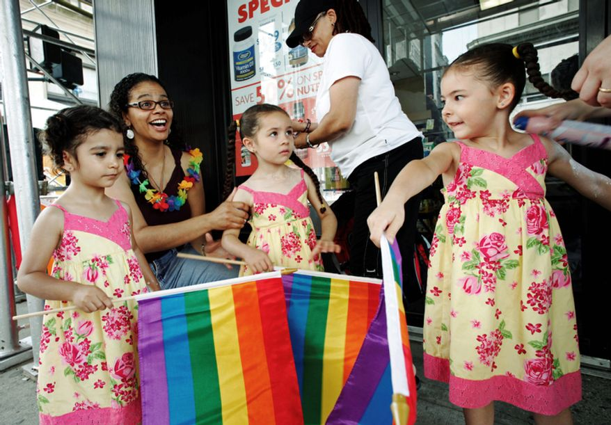 Jennifer Melendez, left, and her wife Juliza, standing, prepare for the annual Gay Pride parade with their daughters Natalia, left, Mahlani, center, and Alexis, Sunday, June 26, 2011 in New York.  (AP Photo/Mark Lennihan)