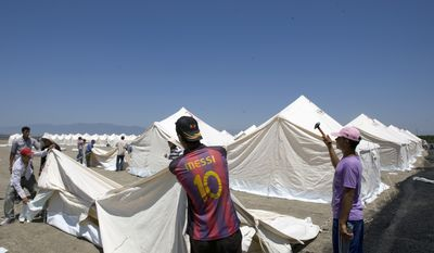 Turkish Red Crescent workers pitch tents in a new camp that can receive up to 15,000 Syrian refugees in Apaydin, Turkey, on Friday, June 24, 2011. (AP Photo/Burhan Ozbilici)