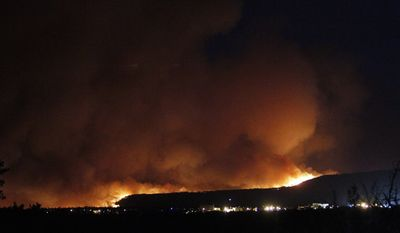 A wildfire crests over the hills above Los Alamos National Labs on June 26, 2011, in New Mexico. (Associated Press/The New Mexican)