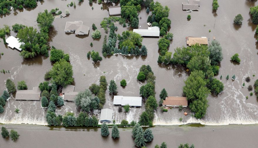 An aerial view of flooded homes in Burlington, N.D.  Just 375 of the 4,000 homes in flooded areas were insured for floods, FEMA spokesman John Ashton said. (AP Photo/Charles Rex Arbogast)