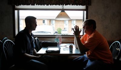FEMA housing inspector Travis Rule, left, from Fort Myers, Fla., talks with Burlington, N.D., resident Vern Erck about his flood damaged home in Minot, N.D. (AP Photo/Charles Rex Arbogast)