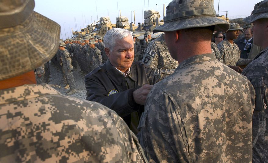 **FILE** In this photo taken Dec. 7, 2010, former Defense Secretary Robert M. Gates pins Combat Infantry badges on soldiers at Forward Operating Base Connolly in Kunar Province, Afghanistan. (Associated Press)