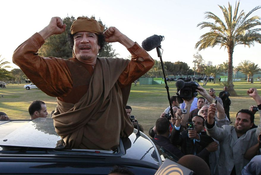 **FILE** In this photo from April 10, 2011, Libyan leader Moammar Gadhafi gestures to his supporters in Tripoli, Libya. (Associated Press)