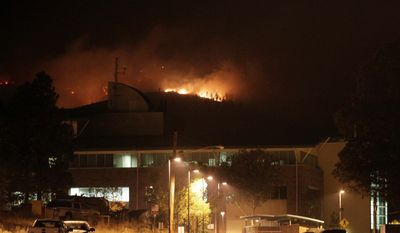 The University of California San Diego's engineering institute at the Los Alamos National Laboratory is illuminated by flames behind it in Los Alamos, N.M., on Tuesday. Thousands of people were driven from their homes, but officials tried to dispel concerns about the safety of sensitive lab materials. (Associated Press)