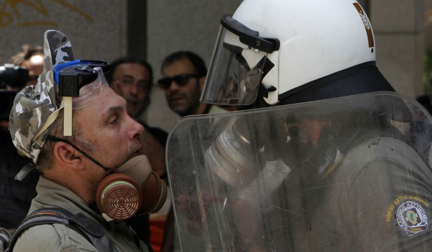 A protester faces a riot police officer during a demonstration in Athens on June 28, 2011. Youths hurled rocks and fire bombs at riot police as a general strike against new austerity measures brought the country to a standstill. (Associated Press)
