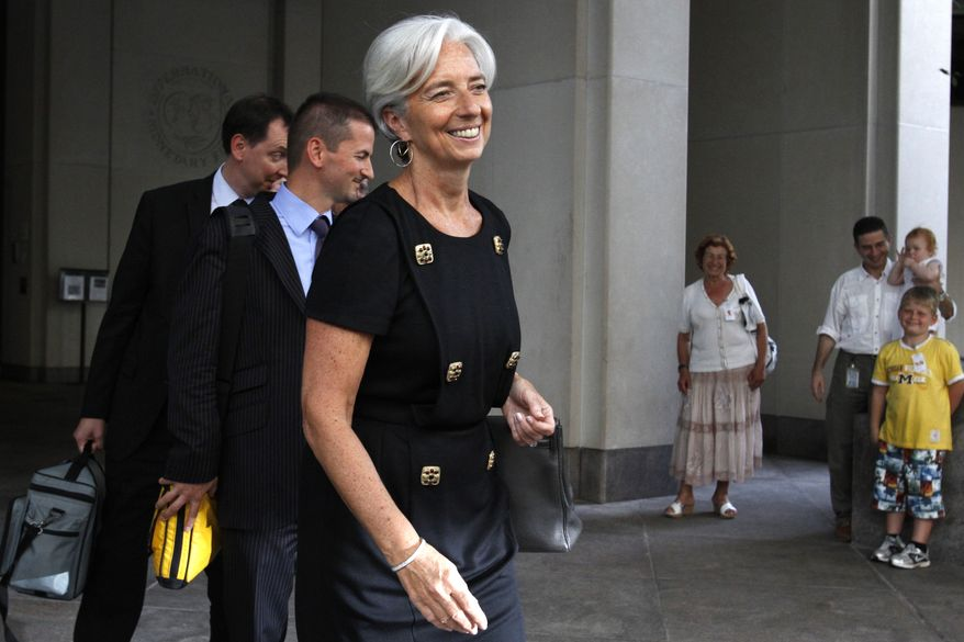 **FILE** French Finance Minister Christine Lagarde (center) exits the International Monetary Fund in Washington on June 22, 2011. She was interviewing in competition to succeed former IMF Managing Director Dominique Strauss-Kahn. (Associated Press)