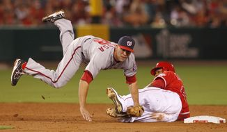 Washington Nationals second baseman Danny Espinosa goes horizontal over Los Angeles Angels' Howie Kendrick to complete a double play in the sixth inning of an interleague baseball game in Anaheim Calif., on Monday, June 27, 2011. (AP Photo/Christine Cotter)