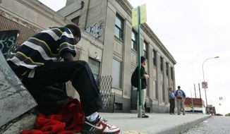 People wait for a bus outside a shuttered art center in Detroit. Mayor Dave Bing is challenging the Census Bureau's count that put the city's population below the important threshold of 750,000, the level needed to qualify for some state and federal aid programs. (Associated Press)
