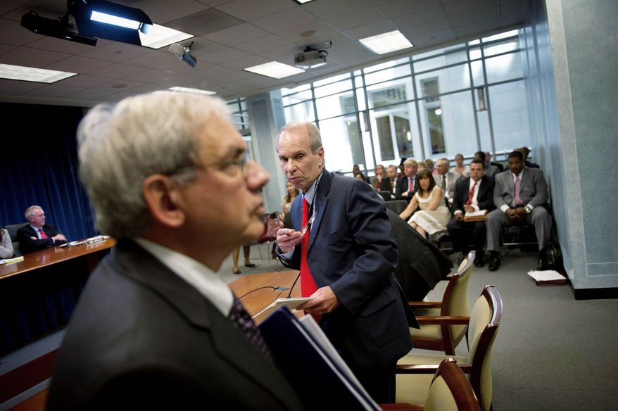 Rod Lamkey Jr./The Washington Times D.C. Lottery chief Buddy Roogow (center) and D.C. Attorney General Irvin B. Nathan (left foreground) attend a D.C. Council committee hearing Wednesday on the lottery's forthcoming online-gambling program. Mr. Nathan said the program complies with federal laws and may proceed toward a September launch .