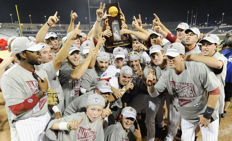 South Carolina players pose with the trophy as they celebrate after beating Florida 5-2 in Game 2 of the NCAA baseball College World Series best-of-three finals, to win the championship, in Omaha, Neb., Tuesday. (AP Photo/Eric Francis)