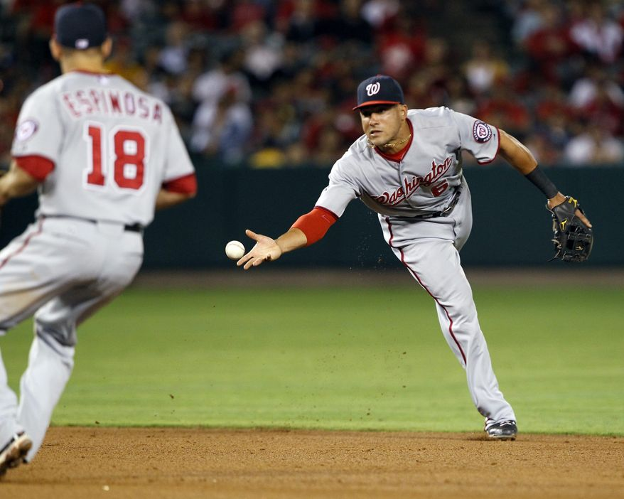 Washington Nationals shortstop Ian Desmond throws the ball to second baseman Danny Espinosa (18) to force out Los Angeles Angels' Mark Trumbo at second base to end the fifth inning of an interleague baseball game in Anaheim, Calif., Tuesday, June 28, 2011. (AP Photo/Alex Gallardo)