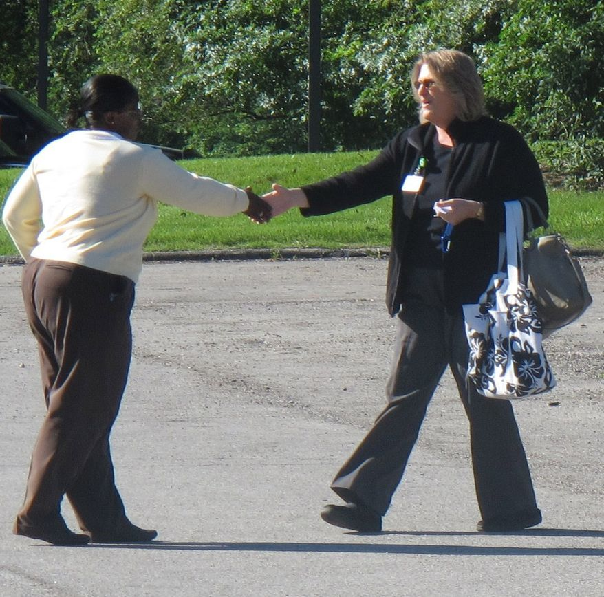 ** FILE ** An employee (left) of a Planned Parenthood clinic in Overland Park, Kan., greets an inspector from the Kansas Department of Health and Environment on Wednesday, June 22, 2011, outside the clinic. (AP Photo/John Hanna)
