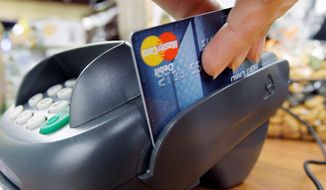 """Retailers may take to court the Federal Reserve's decision nearly doubling the amount banks can charge on """"swipe fees."""" Starting in October, they can charge stores up to 21 cents per transaction every time a customer pays with a debit card. (Associated Press)"""