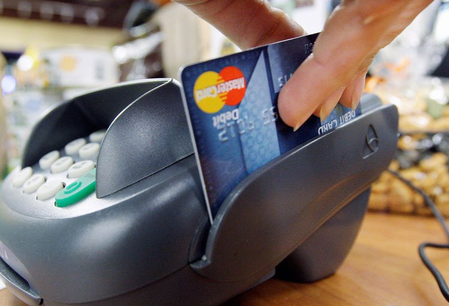 "Retailers may take to court the Federal Reserve's decision nearly doubling the amount banks can charge on ""swipe fees."" Starting in October, they can charge stores up to 21 cents per transaction every time a customer pays with a debit card. (Associated Press)"
