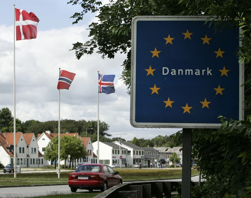 In this photo taken Friday, June 24, 2011, a car crosses the German-Danish border at Krusaa, Denmark. An inattentive driver could easily miss the flags and road signs that mark the border with Germany on the road leading into the small Danish town of Krusaa. On Friday, July 1, 2011, Danish lawmakers will vote on a plan to re-establish permanent customs checkpoints in Krusaa and other border crossings. (AP Photo/Heribert Proepper)