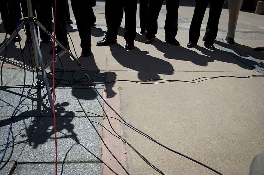 The shadow of U.S. Attorney Rod J. Rosenstein (third from left) is seen on the ground as he makes a statement to reporters that Prince George's County Councilwoman Leslie Johnson, 59, wife of former Prince George's County Executive Jack Johnson, pleaded guilty to the charge of conspiring to obstruct a federal corruption investigation, at the U.S. District Court in Greenbelt, Md., Thursday, June 30, 2011. (Rod Lamkey Jr/The Washington Times)