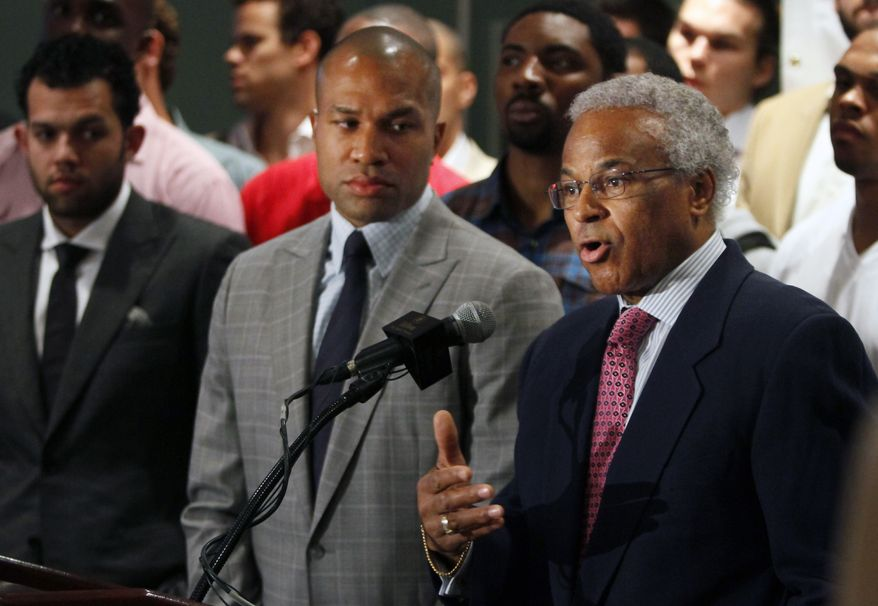 **FILE** National Basketball Players Association union president and Los Angeles Lakers guard Derek Fisher (center) listens as NBPA executive director Billy Hunter (right) speaks during a news conference in New York on June 23, 2011, with NBA players standing behind them. (Associated Press)