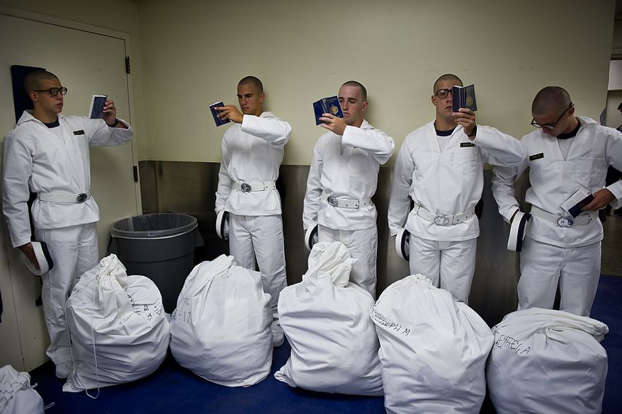 Incoming U.S. Naval Academy students, or plebes, read their Reef Points booklets while waiting with their Navy-issued gear to head to their dormitory on Induction Day at the academy in Annapolis on Thursday, June 30, 2011. The Reef Points serve as an introduction to the Navy, and the plebes are expected to memorize all of the facts in the book. They are instructed to hold the books squarely in front of their face as they read them. (Drew Angerer/The Washington Times)