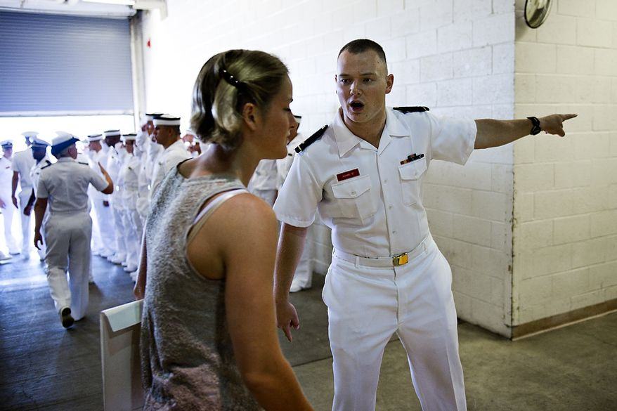 """1/C Matthews Adams (right), a senior at the U.S. Naval Academy in Annapolis, instructs plebes, or first-year students, to walk """"fast and with purpose"""" as they make their way from getting their hair cut to picking up their gear during Induction Day at the academy in Annapolis on Thursday, June 30, 2011. (Drew Angerer/The Washington Times)"""