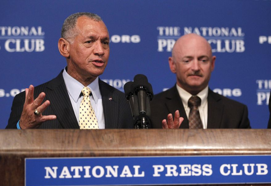 NASA Administrator Charles Bolden (left), accompanied by astronaut Capt. Mark Kelly, husband of wounded Arizona Rep. Gabrielle Giffords, speaks at the National Press Club in Washington on July 1, 2011. (Associated Press)