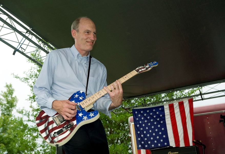 Rep. Thaddeus G. McCotter, Michigan Republican, riffs on his star-spangled Fender Telecaster guitar, much to the delight of supporters, shortly after announcing his candidacy for the Republican presidential nomination at WAAM radio's Fourth of July weekend Freedom Fest in Whitmore Lake, Mich., on Saturday. (Associated Press)