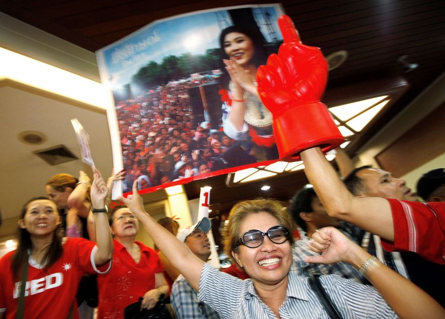 Supporters cheer Yingluck Shinawatra during a rally at the Pheu Thai party's headquarters in Bangkok as she was poised for a landslide victory Sunday. (Associated Press)