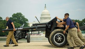 """PHOTOGRAPHS BY DREW ANGERER/THE WASHINGTON TIMES Members of the 3rd U.S. Infantry Salute Guns Platoon move a cannon into position for Monday's Fourth of July celebration on the Mall near the U.S. Capitol, seen in the background (top). The platoon fires the cannon during the performance of Tchaikovsky's """"1812 Overture."""" The team positions one of the cannons to be used (above)."""