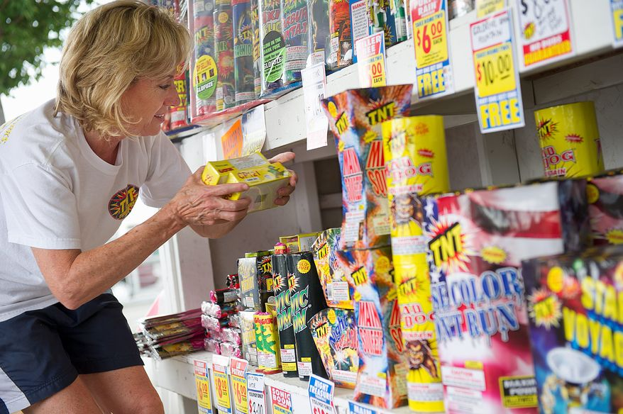 BARBARA L. SALISBURY/THE WASHINGTON TIMES EXPLOSIVE SALES: Jill Halter, of Centreville, stacks fireworks on the shelves at the TNT fireworks stand she is running with daughter Corrin in Manassas, Va.
