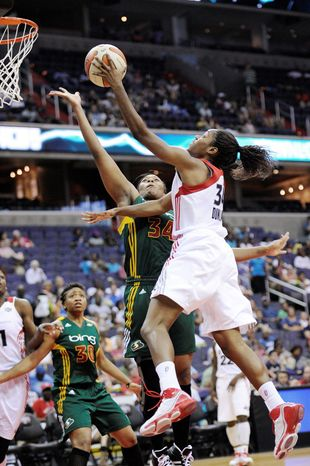 ASSOCIATED PRESS Victoria Dunlap (right) of the Washington Mystics goes to the basket against the Seattle Storm's Le'coe Willingham. Dunlap was playing in place of injured forward Crystal Langhorne.