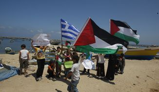 Palestinian children hold Palestinian flags and a blue-and-white Greek flag as they demonstrate in support of the Gaza-bound flotilla in the port of Gaza City, Gaza Strip, on Sunday, July 3, 2011. (AP Photo/Hatem Moussa)