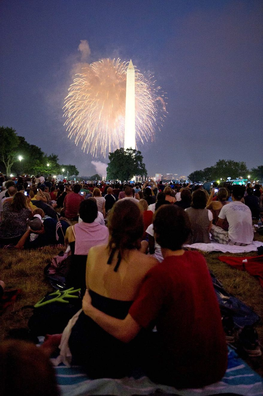 Spectators watch fireworks highlight the Washington Monument on Monday night. Altogether, 14,000 pounds of explosives were used, including a grand finale of 1,000 fireworks ignited in 30 seconds. (Rod Lamkey Jr./The Washington Times)
