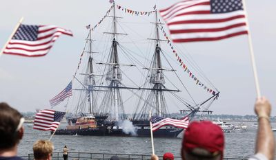 Spectators wave flags as the USS Constitution fires its cannons off Castle Island in Boston on its annual Fourth of July turn around Boston Harbor on Monday, July 4, 2011. (AP Photo/Michael Dwyer)