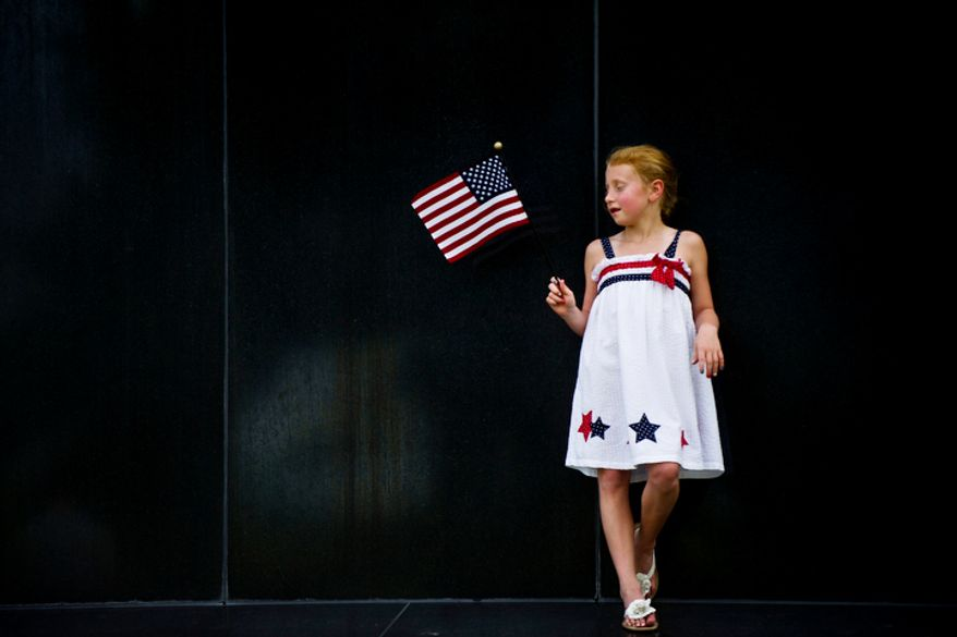 Anne Byrd Fickling, 7, of Fredericksburg, Va., holds an American flag at the base of the Iwo Jima Memorial in Arlington, Va., as she waits for the fireworks to start on Monday, July 4, 2011. (Drew Angerer/The Washington Times)