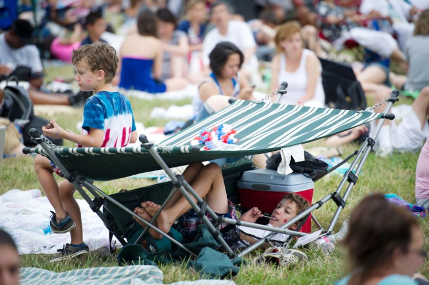 Corydon Swift Turner (under the hammock), 12, and his brother, Afton Swift Turner, 6, of Fairfax, Va., wait for the fireworks as the nation celebrates its 235th birthday on Independence Day in Washington. (Rod Lamkey Jr/The Washington Times)