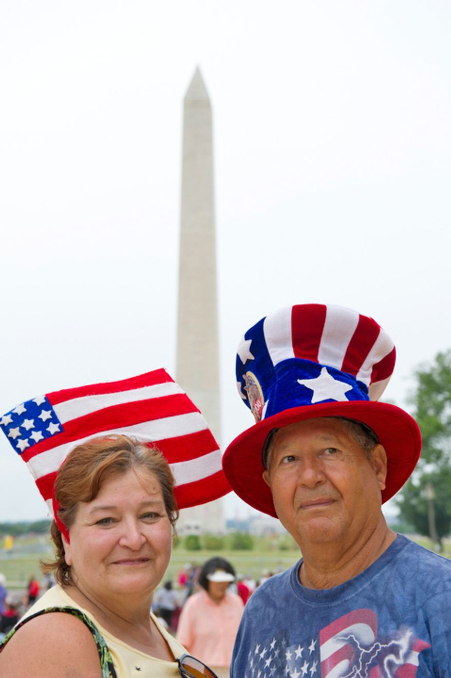Carlos Rodriguez (right) and his wife, Margaret, of Woodbridge, Va., pose in front of the Washington Monument on Independence Day in Washington. (Rod Lamkey Jr./The Washington Times)