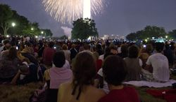 People watch the fireworks over the Washington Monument during the Independence Day fireworks display on the National Mall in Washington on Monday, July 4, 2011. (Rod Lamkey Jr./The Washington Times)
