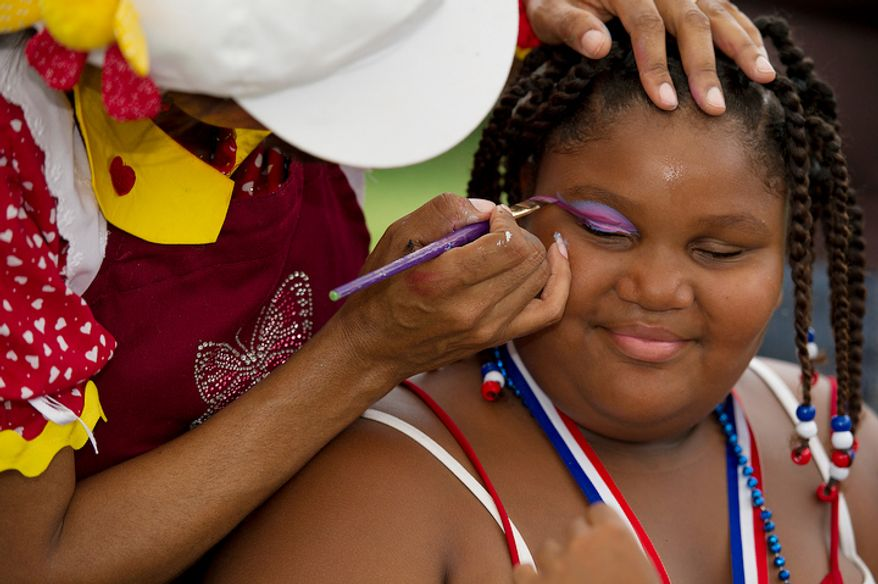 Shawnice Reynolds, 8, of Oxon Hill, Md., smiles as she gets her face painted at the Palisades Recreation Center in Washington on Monday, July 4, 2011. A picnic in the park followed the annual Palisades July Fourth parade. (Barbara L. Salisbury/The Washington Times)