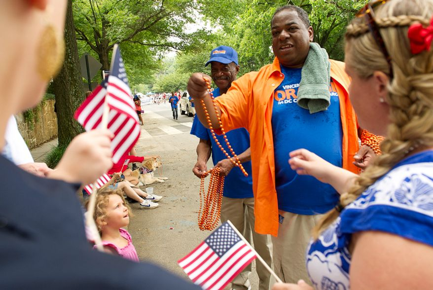 D.C. Council member Vincent Orange hands out orange beads to spectators along MacArthur Boulevard Northwest in the Palisades neighborhood of Washington during the Palisades July Fourth parade. (Barbara L. Salisbury/The Washington Times)