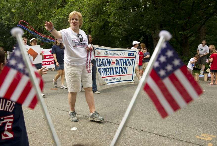 Annalee Ash of Washington tosses out red and blue beads to the crowd while marching with the Taxation Without Representation group in the 45th annual Palisades July Fourth parade in Washington on Monday, July 4, 2011. (Barbara L. Salisbury/The Washington Times)