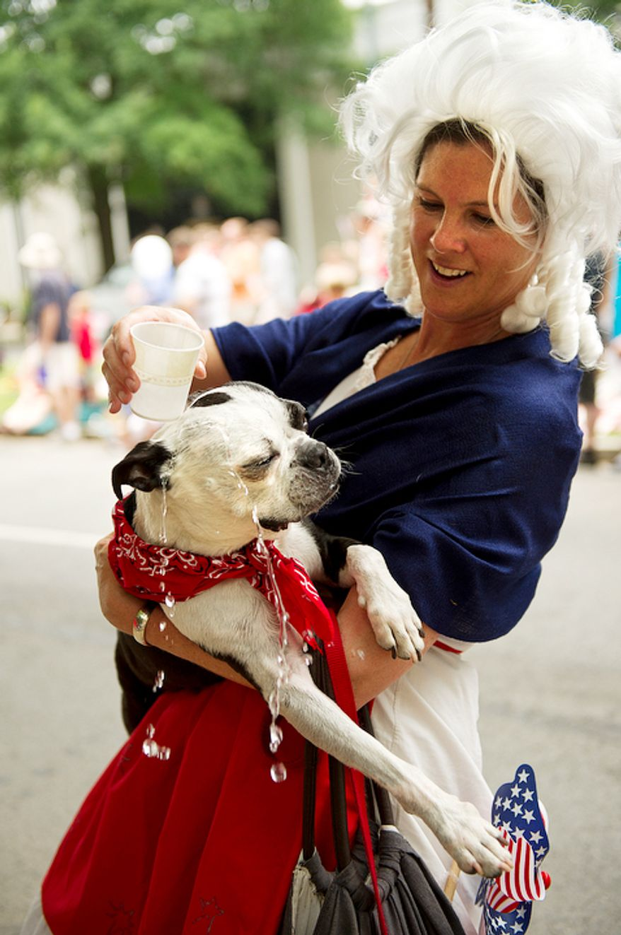 Martha Washington, aka Lalie Tongour, of Washington cools off her dog, Huxley, while marching with the St. Patrick's Episcopal Church contingent in the 45th annual Palisades July Fourth parade. (Barbara L. Salisbury/The Washington Times)