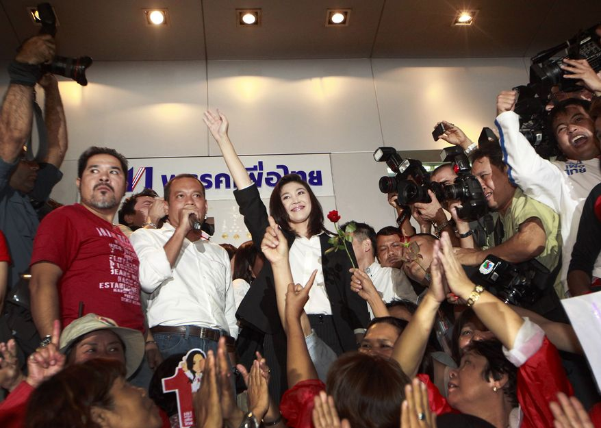 Yingluck Shinawatra (center), leader of Thailand's Phue Thai opposition party, waves to supporters after a press conference at the party headquarters in Bangkok on Sunday, July 3, 2011. (AP Photo/Wason Wanichkorn)