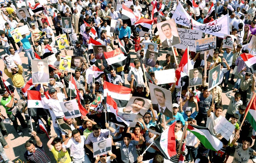 In this photo released by the official Syrian news agency, supporters of embattled Syrian President Bashar Assad hoist pictures of him along with national flags during a rally in the northern city of Aleppo, Syria, on Tuesday. (Associated Press)
