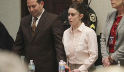 Casey Anthony (center) and her lawyer Jose Baez (left) react to her being found not guilty of murder charges in Orlando, Fla., on July 5, 2011. (Associated Press)