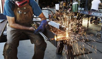 **FILE** In this photo from July 1, 2011, John Rosas, an employee with the metal works factory Wizard of Metals, cuts steel in San Francisco. (Associated Press)