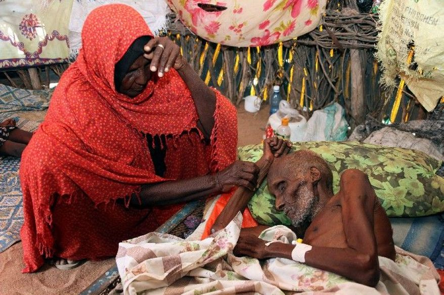 A malnourished Abdi Ibrahim is comforted by his wife, Duba Dagane, as he lies on his bed in Lagbogal, Kenya. Parts of Kenya and Somalia are experiencing pre-famine conditions, the United Nations has said. More than 10 million people are affected in five African nations.
