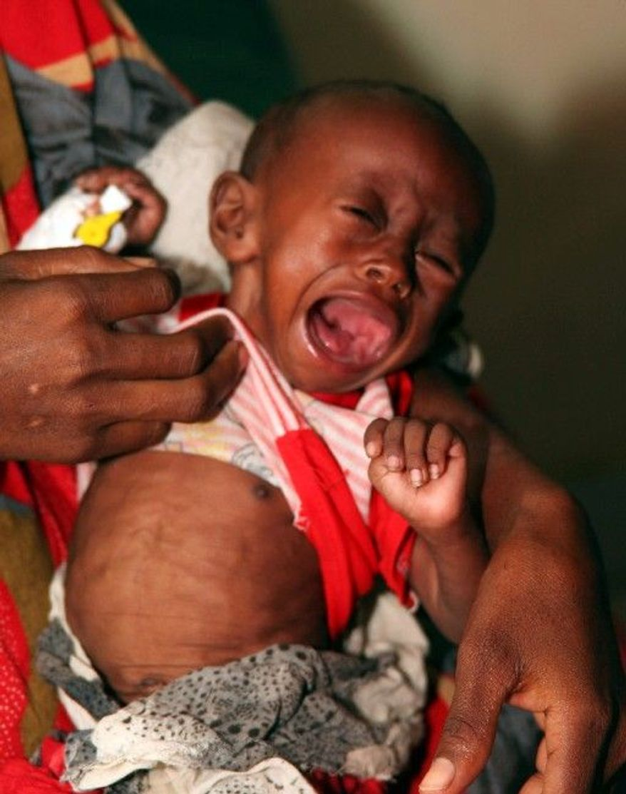 A hungry child cries in her mother's arms, at a hospital in Wajir, Kenya.
