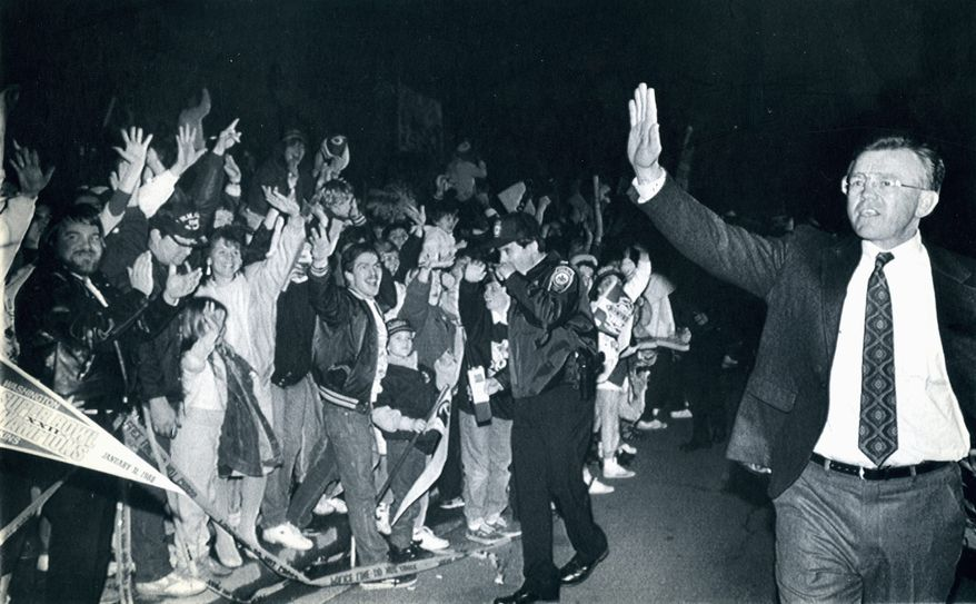 Chantilly, VA Feb, 2, 1988 -- Washington Redskin's head coach Joe Gibbs waves to a welcoming crowd as he and the team arrive back at Redskins Park Monday following Sunday's Super Bowl XXII win over the Denver Broncos. (AP file photo)