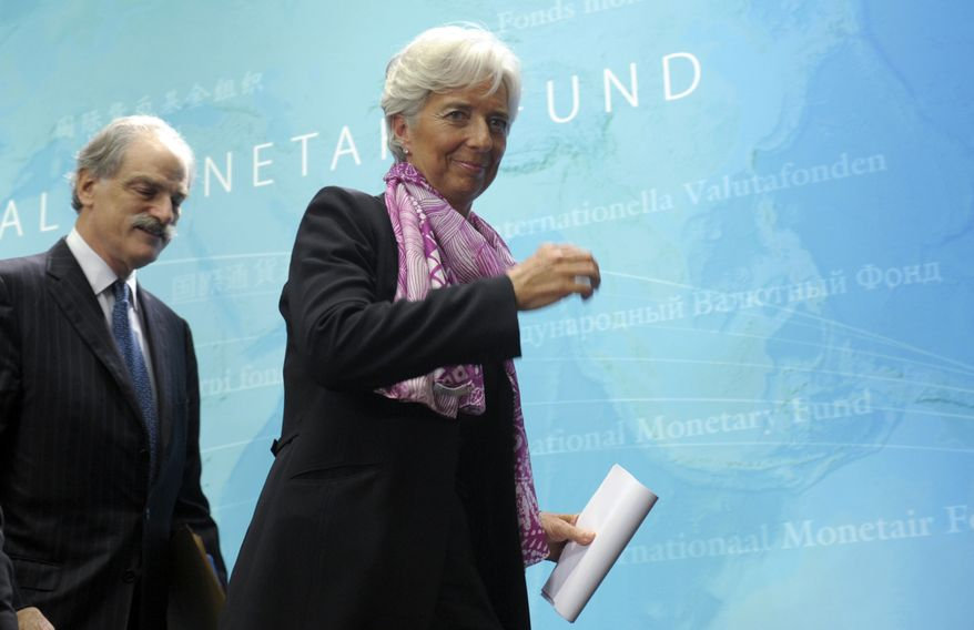 New International Monetary Fund managing director Christine Lagarde (center) walks with John Lipsky, who was acting IMF managing director, as they leave following a news conference at the IMF in Washington on July 6, 2011. (Associated Press)